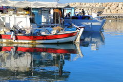 AKAMAS PENINSULA, CYPRUS – NOVEMBER 19, 2015: The reflections of fishing boats in the fishing port of Latsi near Polis. The reflections of fishing boats in the Stock Image