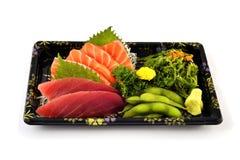 Akami或金枪鱼和三文鱼生鱼片用在交付低成本箱子集合的木豆和辣海草沙拉日本传统食物填装 免版税库存图片
