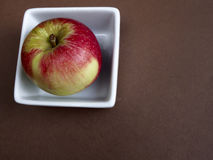 Akane apple. In a bowl on brown background Royalty Free Stock Photos