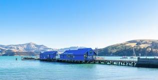 Jetty pier of Akaroa, south island of New Zealand. People can seen exploring around it. Akaroa,New Zealand - May 12,2016 : Jetty pier of Akaroa, south island of Royalty Free Stock Image