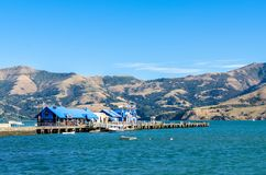 Jetty pier of Akaroa, south island of New Zealand. People can seen exploring around it. Akaroa,New Zealand - May 12,2016 : Jetty pier of Akaroa, south island of Stock Photography