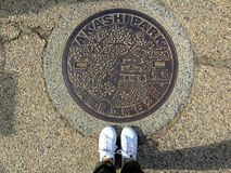Female legs standing in front of a decorated Manhole in Akashi park stock photos