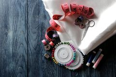 Akcesoria dla szyć i uszycia nici, tkanina, nożyce, bobiny, szpilki, centymetr na zmroku - błękitny drewniany tło z a obraz royalty free