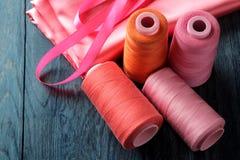 Akcesoria dla szyć, uszycie tkaniny i nici nożyc na zmroku i - błękitny drewniany tło fotografia stock