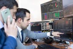 Akcyjni maklery patrzeje ekrany komputerowych, handluje online Zdjęcie Royalty Free