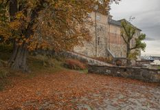 Akershus Fortress, Oslo - autumnal leaves on the ground. Akershus Fortress or Akershus Castle is a medieval castle that was built to protect and provide a royal royalty free stock image