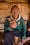 Akha族群逗留的一个老人在他的竹房子附近的,抽烟与一个木管子 免版税库存图片