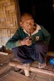 Akha族群逗留的一个老人在他的竹房子附近的,抽烟与一个木管子 免版税库存照片