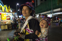 Akha in Chiangmai city. The Akhas woman in ChiangMai City raising her child during work at night, this hill tribe people can speak very little of Thai language royalty free stock image