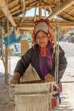 Akha woman weaving fabrics in traditional way in Akha village, Northern Thailand. Chiang Rai, Thailand - February 8, 2017: Akha woman weaving fabrics in Stock Image