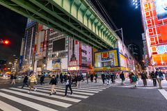 Unidendified people walk across the street in Akihabara at night, Tokyo, Japan royalty free stock photography