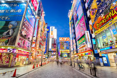 Akihabara Tokyo Japan. TOKYO, JAPAN - AUGUST 1, 2015: Crowds pass below colorful signs in Akihabara. The historic district electronics has evolved into the Stock Images