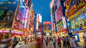 Akihabara Tokyo Japan. TOKYO, JAPAN - AUGUST 1, 2015: Crowds pass below colorful signs in Akihabara. The historic district electronics has evolved into the