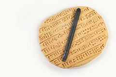 Akkad empire style cuneiform written in brown clay with writing tool. Ancient type of Akkad empire style cuneiform writing in brown clay Royalty Free Stock Photo