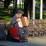 Akkordeonspieler, der auf Bank im Stadtpark, Wien, Österreich sitzt Stockfotografie