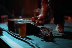 Akoestisch gitaar en bier op stadium bij een jol stock foto