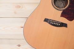 Akoestische gitaar die tegen een houten achtergrond rusten stock fotografie