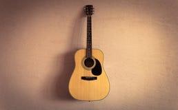 Akoestische gitaar op beige uitstekende muur als achtergrond Stock Foto