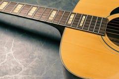 Akoestische gitaar op marmeren dichte omhooggaand stock afbeelding