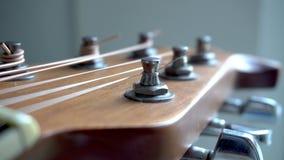 Akoestische gitaar stemmende pinnen met koorden stock footage