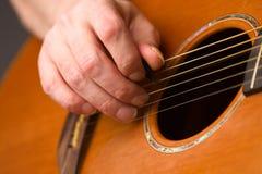 Akoestische gitaarspeler die plectrum gebruikt Stock Foto's