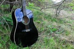 Akoestische zwarte gitaar in het hout Royalty-vrije Stock Foto