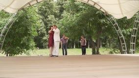Akordeon i skrzypce bawić się w parku Kobieta w czerwonej sukni i mężczyzna w białym kostiumu tanczymy tango Starsze osoby zbiory wideo