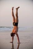 Akrobat auf dem Strand stockbild