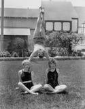 Akrobat, der auf den Schultern der Frauen balanciert (alle dargestellten Personen sind nicht längeres lebendes und kein Zustand e Stockbild