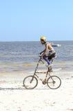 Akrobat mit einem doppelten Fahrrad auf dem Strand Stockbilder