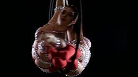 Akrobat två gör in beståndsdelen i det flyg- beslaget Svart bakgrund långsam rörelse close upp lager videofilmer