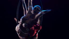Akrobat två gör in beståndsdelen i det flyg- beslaget Svart bakgrund långsam rörelse close upp arkivfilmer