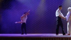 Akrobater utför trick under barn kopplar ihop allsångsången, etapp av teatern arkivfilmer