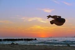 Akrobatik auf dem Meer, Akrobat bei Sonnenuntergang der Seeküste, Salto auf dem Strand lizenzfreies stockbild