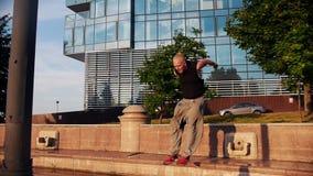Akrobatischer blonder Mann, der oben und Hindernisse mit parkour Tricks überwinden läuft stock video