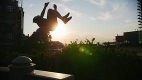 Akrobatischer Mann, der einen leichten Schlag auf einem schmalen Stand außerhalb - des Sonnenuntergangs durchführt stock footage
