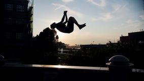 Akrobatischer Mann, der einen leichten Schlag auf einem Stand außerhalb - des Sonnenuntergangs durchführt stock video