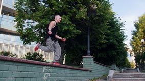 Akrobatischer Mann, der oben läuft und von einem Stand zu anderen springt stock video