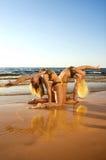 Akrobatisches Mädchen zwei auf dem Strand Stockfotos