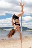 Akrobatisk kapacitetsbrunett i baddräkt på polen för att dansa Royaltyfri Foto