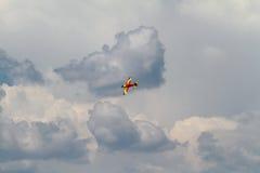 Akrobatiskt flygplan på mörka moln Arkivfoto
