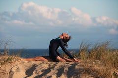 Akrobatyczna gimnastyczka robi rozłamowi na plaży Zdjęcia Royalty Free