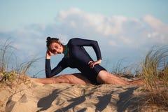 Akrobatyczna gimnastyczka robi rozłamowi na plaży Fotografia Royalty Free