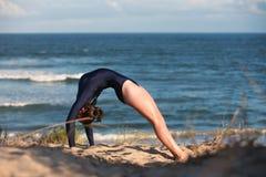 Akrobatyczna gimnastyczka wysklepia ona na plaży z powrotem Fotografia Royalty Free