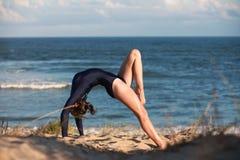 Akrobatyczna gimnastyczka wysklepia ona na plaży z powrotem Obraz Stock
