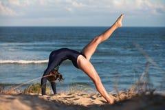 Akrobatyczna gimnastyczka wysklepia ona na plaży z powrotem Obrazy Royalty Free