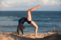Akrobatyczna gimnastyczka wysklepia ona na plaży z powrotem Obrazy Stock