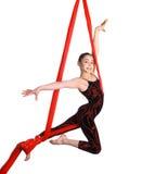 Akrobatyczna młoda dziewczyna ćwiczy na czerwonej tkaniny arkanie Fotografia Royalty Free