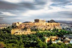 Akropol med Parthenon Sikt till och med en ram med gröna växter, träd, forntida marmor och cityscape, Aten arkivfoton