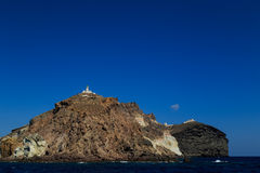 The Akrotiri Lighthouse in Santorini surrounded by the sea. royalty free stock photography